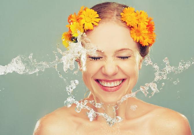 Frau mit Wasser vor dem Gesicht.