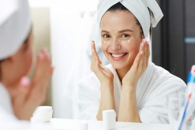 Frau vor dem Spiegel versucht durch Pflege das Hautbild zu verbessern