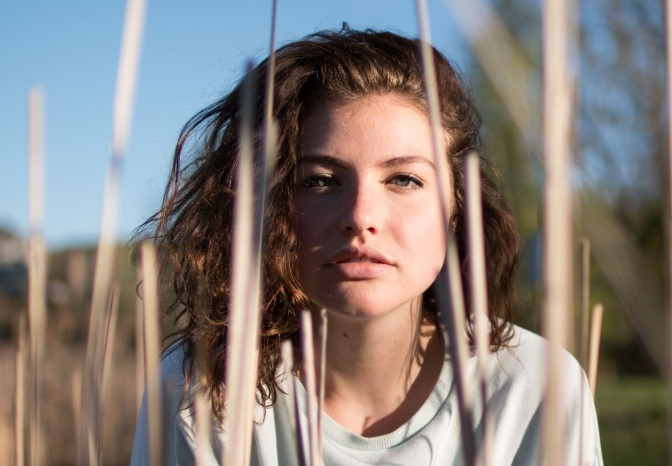 Eine Frau sitzt im Gras und will das Hautbild verbessern