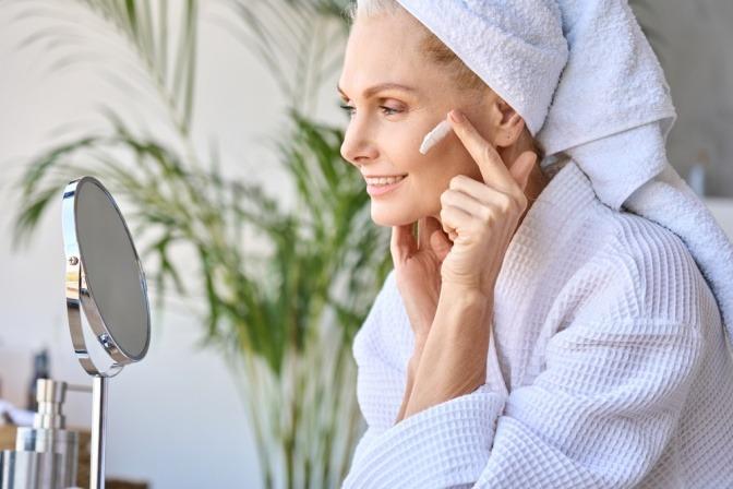 Frau pflegt trockene Haut im Gesicht