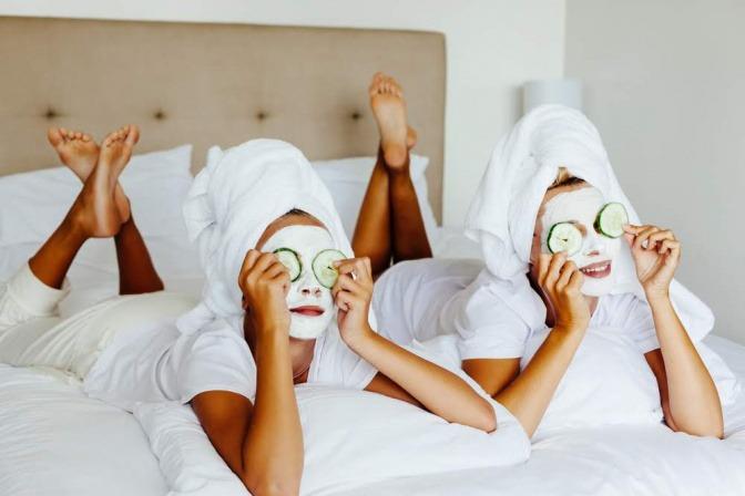zwei Frauen mit Gesichtsmasken und Gurken auf den Augen