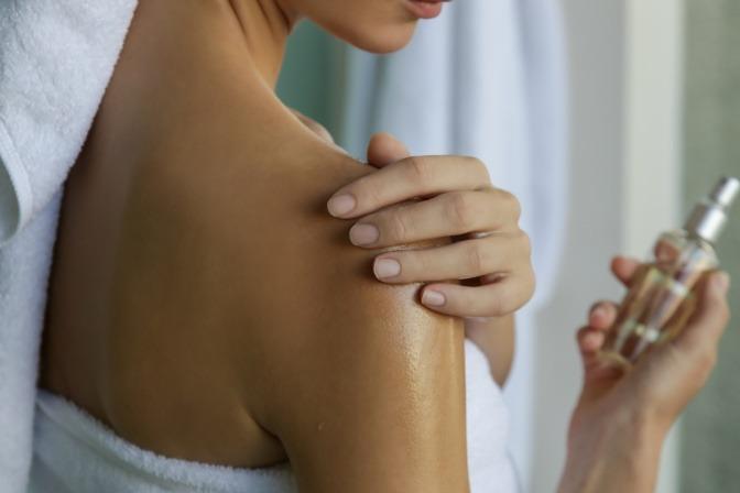 Frau ölt nach dem Duschen ihre Haut ein