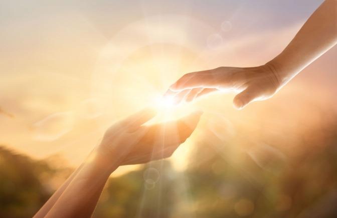 Zwei Hände reichen einander, dahinter Licht als Zeichen für Seelenfrieden