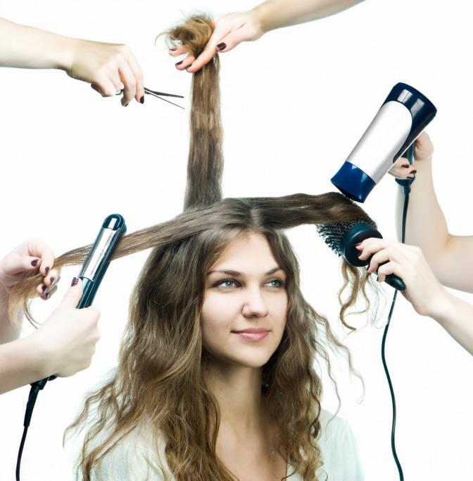 Frau deren lange Haare die mit Fön, Glätteisen und  Bürste bearbeitet werden