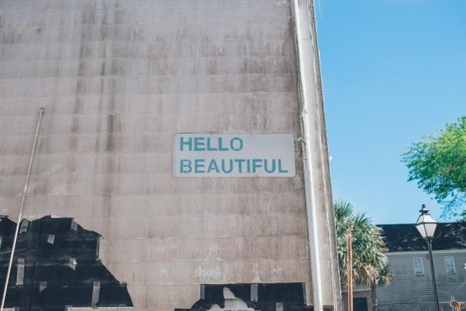 Auf einer Hausmauer steht hello beautiful