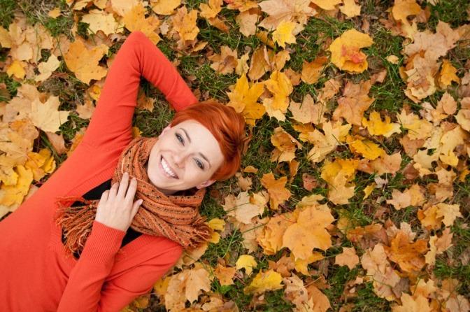 Eine Frau liegt auf einer herbstlichen Wiese und weiß, wie man das Immunsystem stärken kann