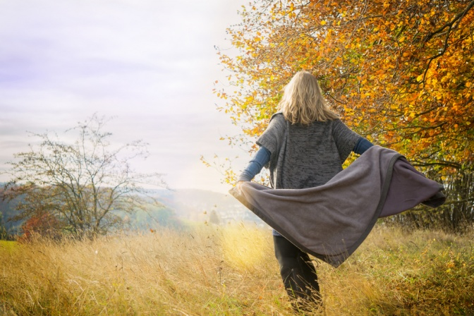 Frau in Herbstlandschaft von hinten