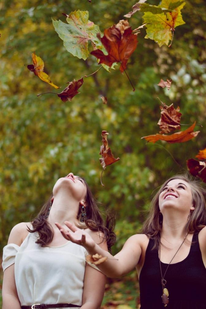Zwei Frauen werfen Blätter im Herbst in die Luft