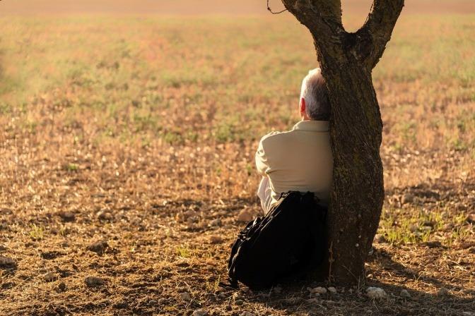 Ein immunstarker Mann sitzt im Herbst an einen Baum gelehnt