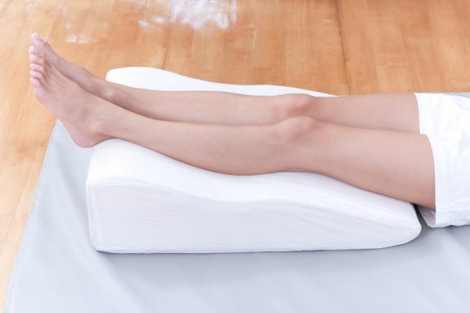Beine auf einem Keilkissen