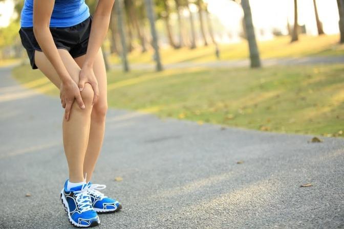 Eine joggende Frau hat auf einer Straße angehalten und fasst sich an das rechte Knie.