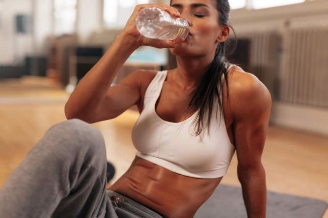 Eine stark verschwitzte Frau in einem Trainingsraum macht zwischen HIIT Übungen eine Pause und trinkt Wasser aus einer Flasche.