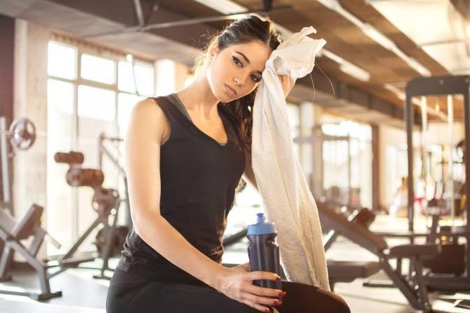 Eine Frau sitzt nach einem anstrengenden HIIT Training in einer Sporthalle auf einer Trainingsmatte und wischt sich mit einem Handtuch die Stirn.