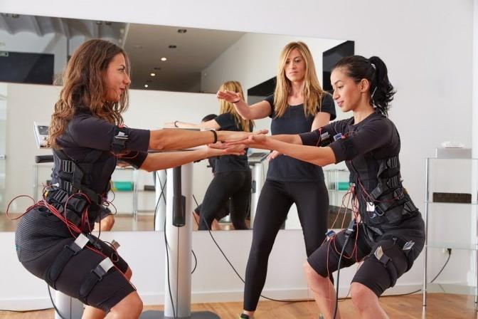 Eine Trainingssituation mit zwei Sportlerinnen und einem weiblichen Coach. Die Sportlerinnen knien auf dem Boden und machen eine Partnerübung. Beide tragen jeweils einen Gummianzug, an dem viele Kabel und Drähte angebracht sind.