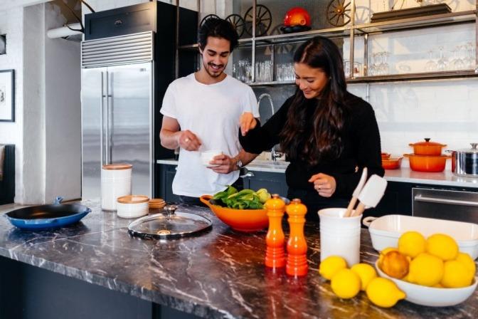 Eine Frau und ein Mann kochen als Hobby zu Hause