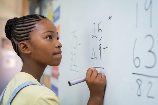 Ein Mädchen erledigt mathematische Aufgaben an der Tafel