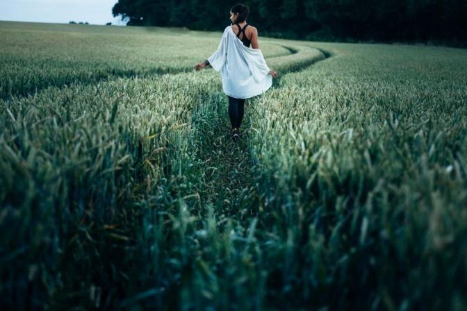 Eine Frau folgt einem Weg im hohen Gras