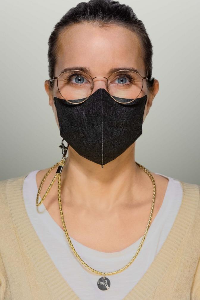 Eine Frau trägt eine Maske mit einem Holdie Maskenband
