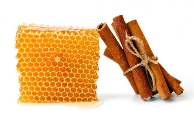 Ein Bündel Zimtstangen lehnt an einer Honigwabe.