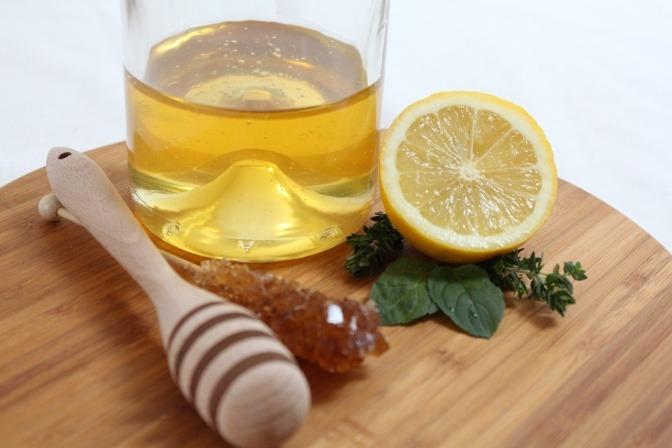 Eine halbe Zitrone liegt neben Honig