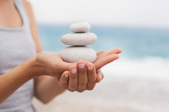 Eine Frau hält Steine in Balance auf ihrer Hand
