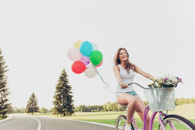 Frau am Fahrrad als Symbol für Gleichgewicht