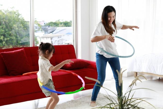 Mutter und Tochter machen Hula Hoop