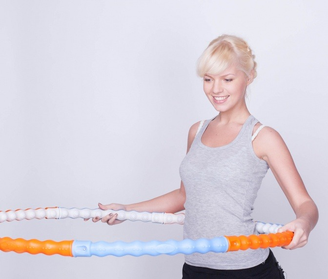 Eine Frau legt ihren Hula Hoop Reifen zum Training an