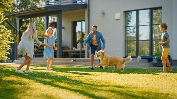 Eine Familie spielt im Garten mit einem Golden Retriever.