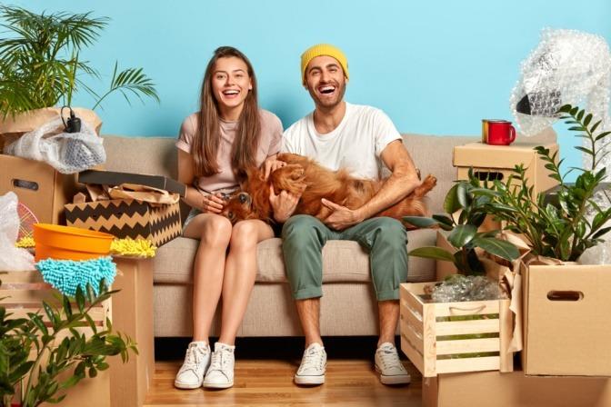 Hund ja oder nein? Diese Frage hat das Paar, welches in diesem Bild mit seinem Hund auf der Couch schmust, eindeutig positiv beantwortet.