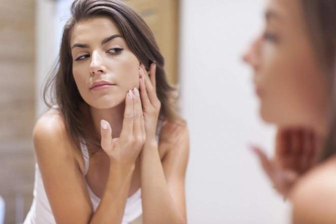 Frau im Spiegel die ihre hypersenible Haut behandelt