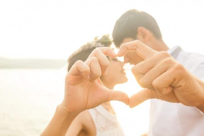 Ein Paar ist am Strand, während des Sonnenuntergangs am Strand und formt dabei ein Herz mit den Händen.