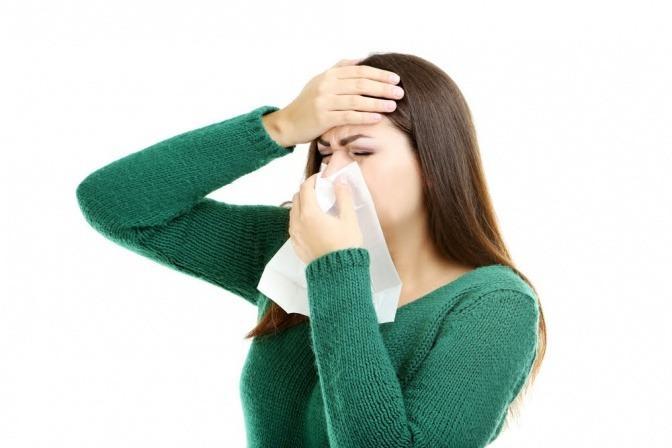 Frau hat eine Infektion und putzt sich die Nase