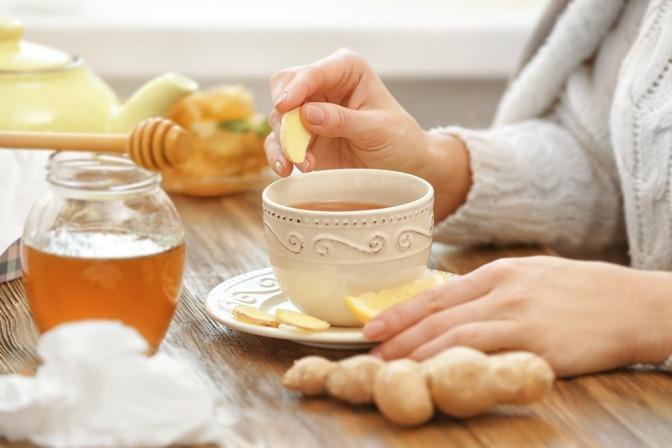 Eine Frau bereitet Tee mit Ingwer gegen Übelkeit