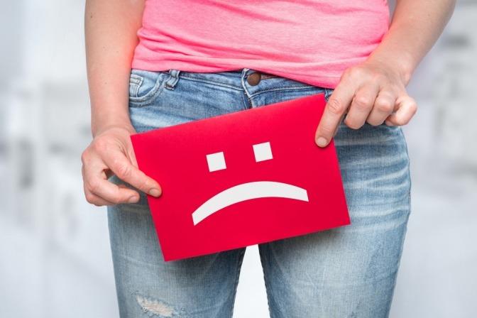 Frau hält Schild mit traurigem Smiley als Zeichen für Inkontinenz