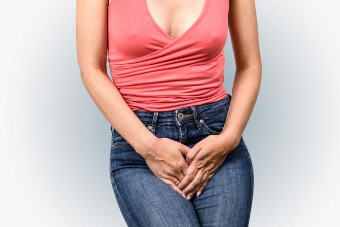 Eine Frau hält ihre Hände auf den Unterleib als Zeichen für Inkontinenz