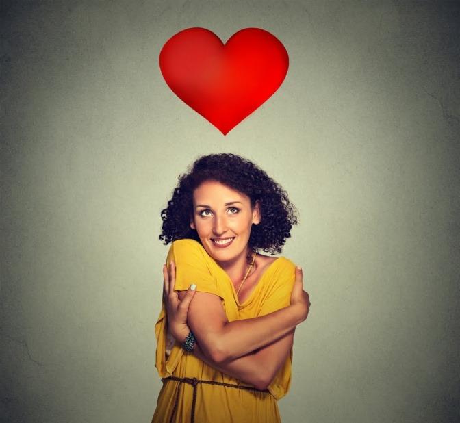 Eine Frau umarmt sich selbst und sie lächelt dabei. Über ihrem Kopf schwebt ein großes rotes Herz.