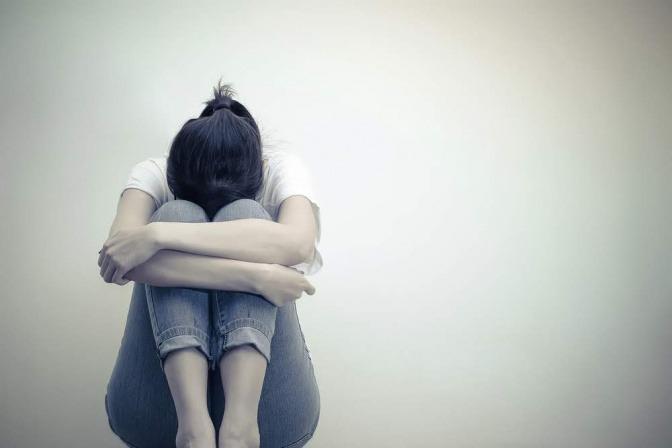 Eine Frau sitzt zusammengekauert auf dem Boden und vergräbt ihr Gesicht in den angewinkelten Beinen. Vielleicht denkt sie darüber nach, wie sie ihre innere Leere überwinden kann.