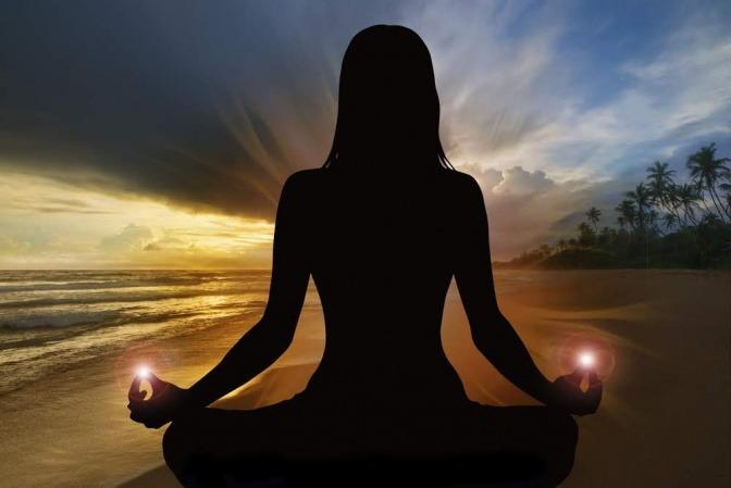 Eine Frau sitzt im Schneidersitz am Strand und meditiert.