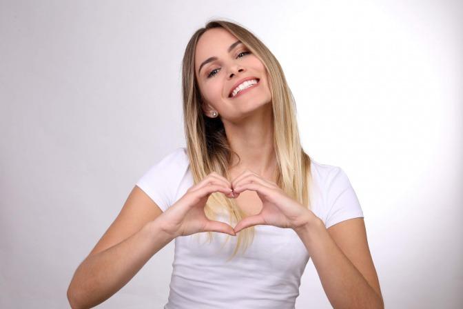 Eine glückliche und zufriedene Frau lächelt in die Kamera und formt dabei mit ihren beiden Händen ein Herz vor ihrem Bauch.