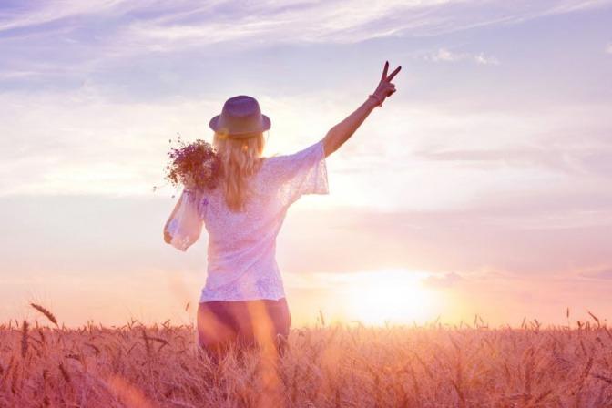 Eine Frau steht bei Sonnenuntergang in einem Blumenfeld und macht mit der rechten erhobenen Hand das Victory-Zeichen.
