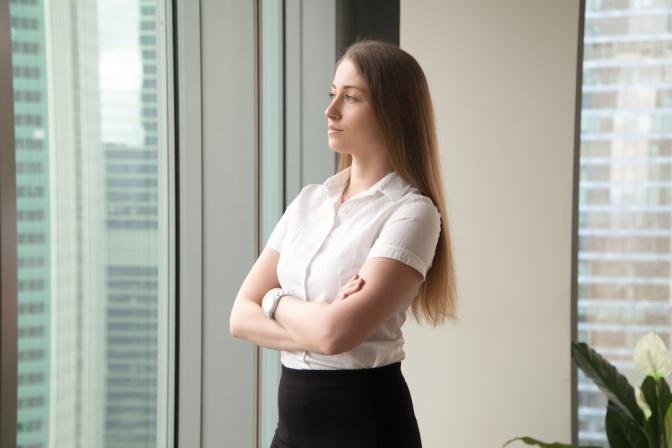 Eine Frau steht vor dem Fenster und will ins Wohlbefinden zurückfinden