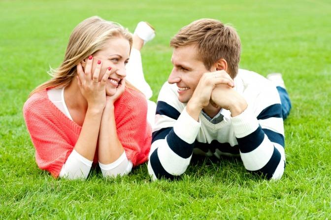 Ein Paar himmelt sich an, während die Partner nebeneinander auf einer Wiese liegen.