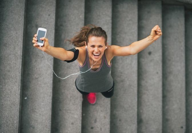 Eine Joggerin springt nach dem Erklimmen von Stufen in die Luft. Sie wirkt fröhlich.
