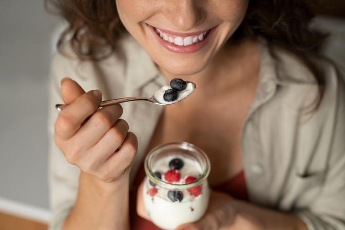 Eine Frau genießt einen Becher Naturjoghurt mit frischen heimischen Beeren.