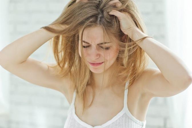 Frau mit gereizter und juckender Kopfhaut