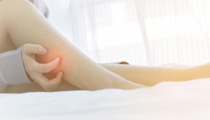 Frau die ihre Beine kratzt