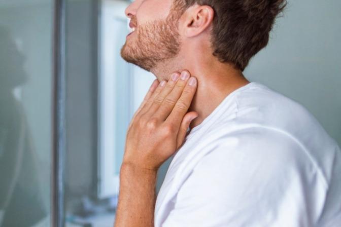 Ein Mann greift auf seinen rasierten Hals