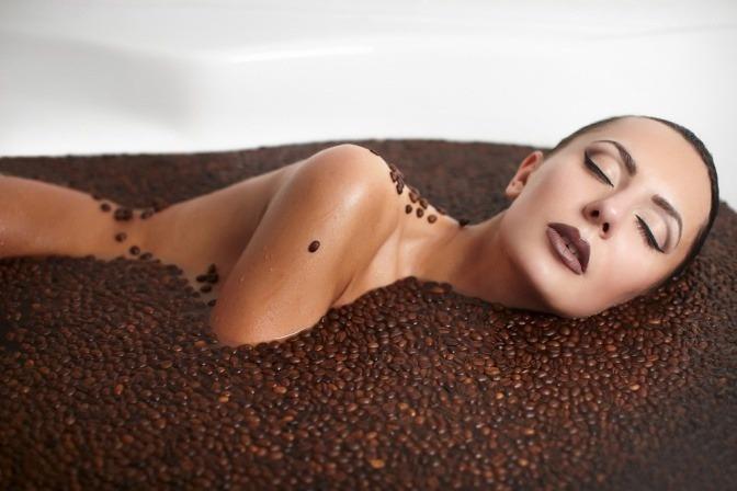 Eine Frau liegt in Kaffeebohnen