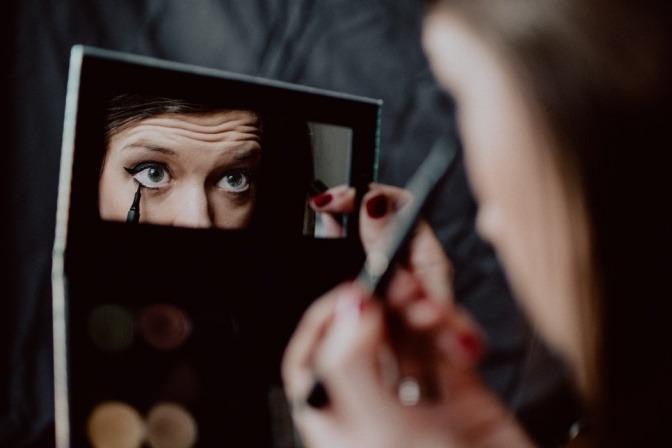 Eine Frau schaut in einen Spiegel und trägt schwarzen Kajal in der unteren Wasserlinie auf